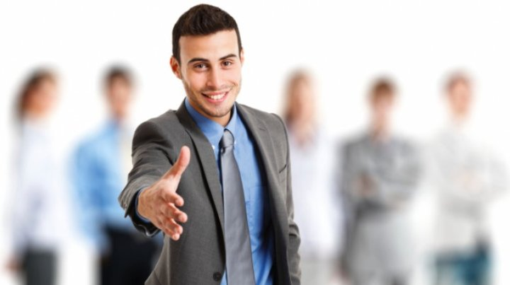 Businessman giving an handshake in front of his team