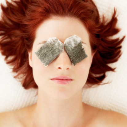 woman lying with tea bags on her eyes