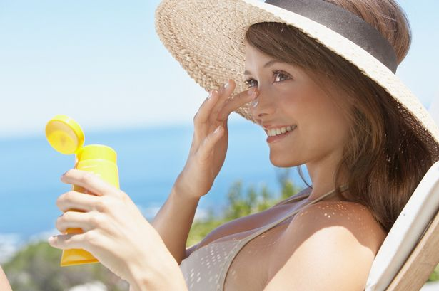Woman-with-straw-hat-applying-sun-block-to-face-outdoors