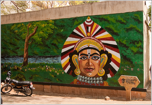 Lately Bangalore walls are being painted by small-time painters with murals and paintings in a bid to beautify the city. Featured here is a Yakshagana headgear. This is on a wall opposite the famous Rangashankara theatre.